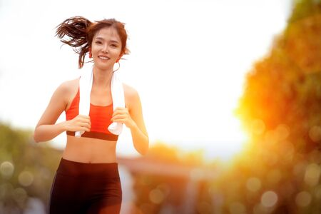 Asian girl running in her village with sportswear and morning sunrise background this image can use for sport and health concept Reklamní fotografie