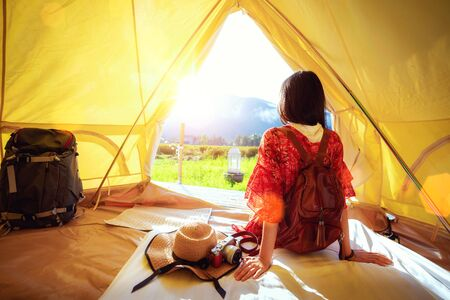Asian girl relax inside tent in Countryside homestay in rice farm in Pua District, Nan province, Thailand. This image can use for home stay, hotel, resort, holiday, travel, park and outdoor concept