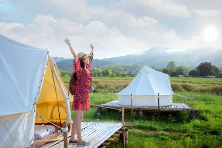 Asian girl happy and relax inside tent in Countryside homestay in rice farm in Pua District, Nan province, Thailand. This image can use for home stay, hotel, resort, holiday, travel, park and outdoor concept