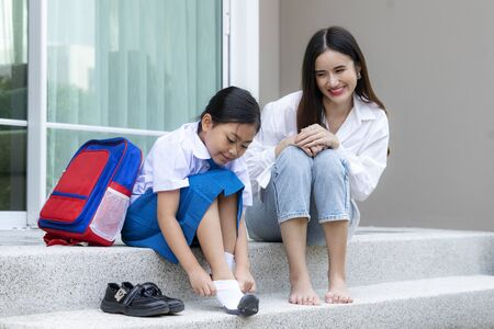 s in uniform to wearing their own shoes infront of home to prepare for school in the fine weather morning. Parenthood or love