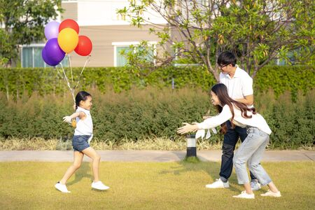 Asian daughter run with balloon on hand to her mother and her father in her village, this image can use for family, love and park concept