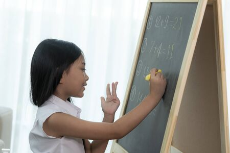 Asian girl write and do home work on the backboard before back to school, this image can use for school, education and intelligent concept