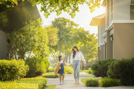Asian preschool girl walk with her mother to go to school with gardent in morning time background