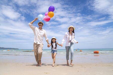 Asian Family having fun running on a sandy beach in Pattaya, Thailand Stock Photo