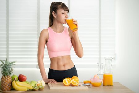 Asian girl make an orange juice by hand at home after finished exercise, this image can use for fruit, clean food and eat health concept