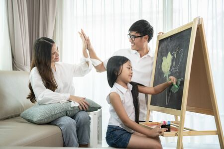 Asian family happy happy after teach they daughter to draw a flower in backboard