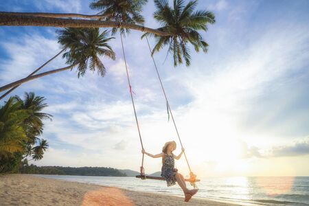 Asian girl on swing in Koh Kood island with coconut and beach background, trat, Thailand
