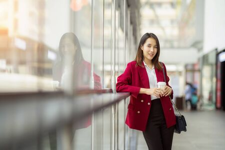 young office worker girl holding hot espresso paper cup leisurely walking on glass wall background thinking about work planning relax during lunch break time.