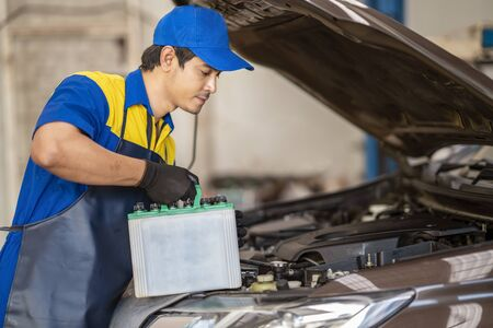Action of man hands using spanner remove car battery terminals to change the new one, car fixing and maintenance service concept.