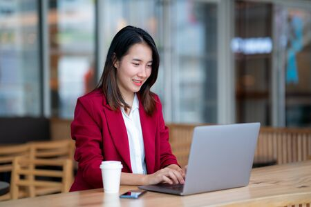 Young business woman in red suit sitting at table in cafe bar and typing in notebook. Freelancer working in coffee shop with laptop computer. girl worker enjoy cup of coffee in city coffee shop.