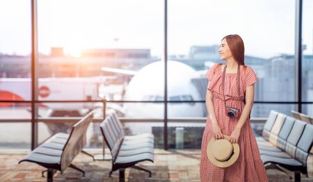 Travel tourist standing with luggage watching sunset at airport window. Unrecognizable woman looking at lounge looking at airplanes while waiting at boarding gate before departure. Travel lifestyle. Zdjęcie Seryjne