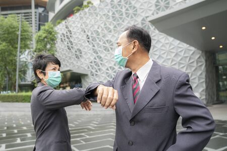 Old asian business people greeting togather by new methode with mask for prevent covid 19, this image can use for covid-19, coronavirus and shakehands concept.