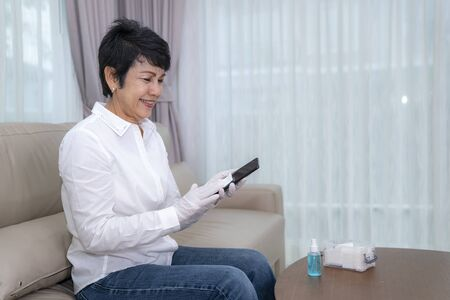 old people clean her mobile phone for prevent a covid 19 virus by alcohol.