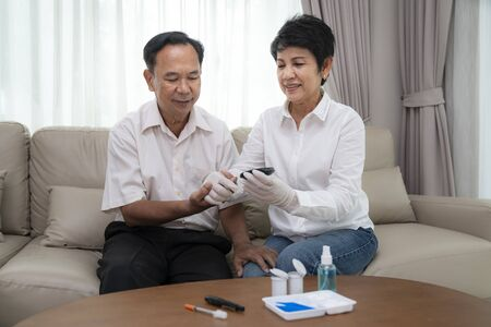 Asian old man and him wife test diabetes check  by them self in they home. 写真素材
