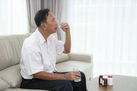 An asian old man is going to take some pills