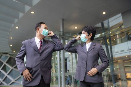 Old asian business people greeting togather by new methode with mask for prevent covid 19, this image can use for covid-19, corona virus and shakehands concept.