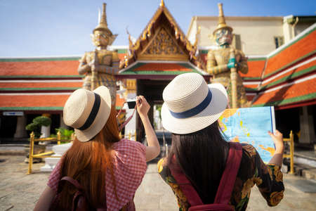 Two asian girlfriends traveling and check location by a map in Grand Palace and Wat phra kaew Bangkok city,Thailand Imagens