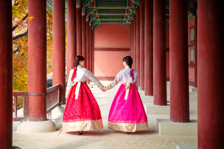 Asian girl walk in autumn leaves park and old palace in seoul city, south korea.