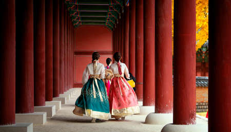 Asian girl in hanbok dress walk in autumn leaves park and old palace in seoul city, south korea.