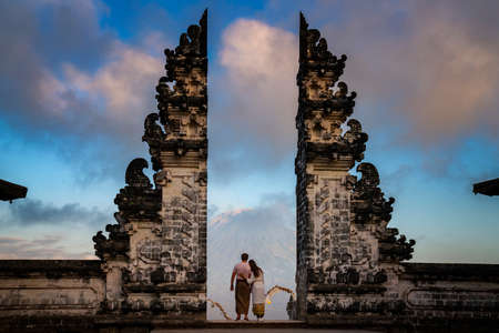 Happy young couple staying in temple gates of heaven and holding hands of each other. Perfect Honeymoon concept. Lempuyang Luhur temple in Bali, Indonesia. Imagens