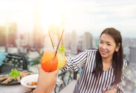 Asian working woman drink mojito cocktail with her girl friend in restaurant on building rooftop with Bangkok city background. Imagens