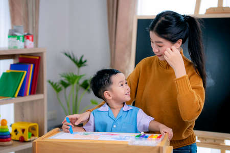 Asian teacher in classroom on preschool teach her student to drawing on paper by color pencil on the table with backbord background, this image can use for back to school and education concept.