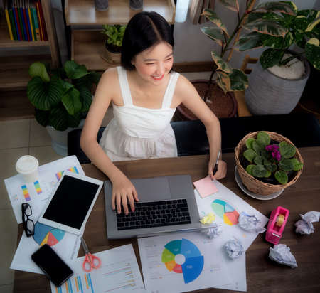 Asian woman work from home by use conputer notebook in her home office, this image can use for covid19, business and plant decor concept Imagens