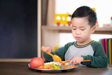 Asian student take a lunch in class room by food tray prepared by his preschool, this image can use for food, school, kid and education concept Imagens