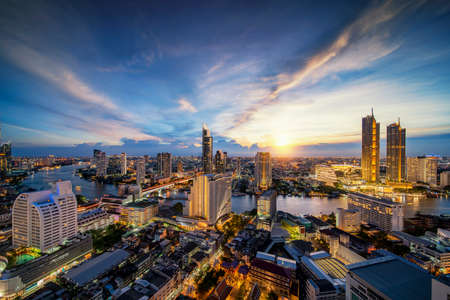 Cityscape in Bangkok city from roof top bar in hotel with Chao phraya river background, this image can use for Bangkok, Thailand, Night, tourist and asia concept.