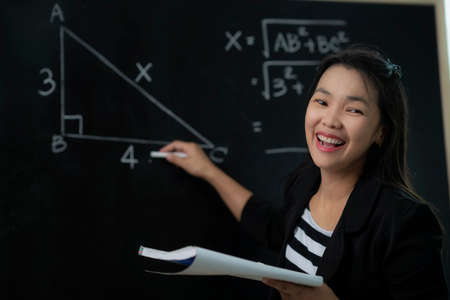 Asian teacher explane mathematics formula to her student in classroom, this image can use for education, job, teacher, tutor and school concept Imagens