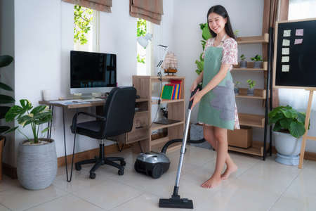 Young asian woman hoovering floor at home, this image can use for cleanup, housework, office, job and vacuum cleaner concept Imagens