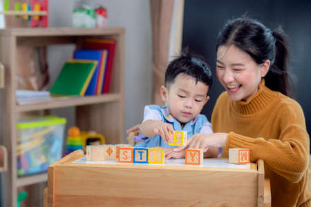 Asian student in preschool use a letter box make a study word in class room with his teacher, this image can use for genius, clever, education and school concept. Standard-Bild