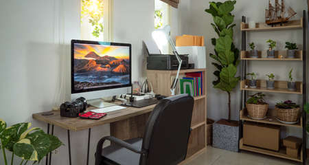 Small homeoffice for photographer with plants decor and Bromo Mt picture on the destop wall paper of his computer, this image cau use for sme, home, office and studio concept