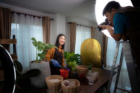 Photographer take photo for Plant a tree concept by asian lady model in his studio