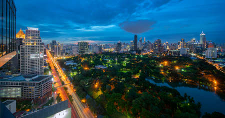 View point from roof top bar in hotel of Bangkok city with Green zone area and business center area on sunset time. Imagens