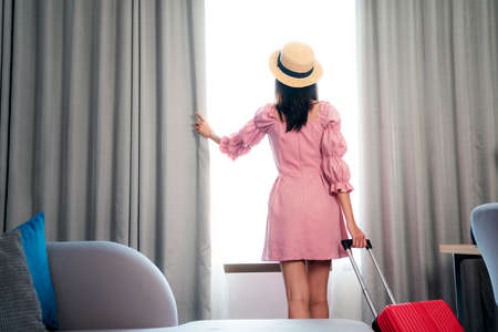 Asian woman traveller in pink dress arrive to room in hotel and open curtain for enjoy with outside view, this image can use for Travel, tour, hotel and travel insurance concept