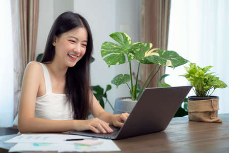 Asian girl typing data to her computer notebook for prepare her report on the wooden deak with the green plant on the table, this image can use for education, office, university and student concept.