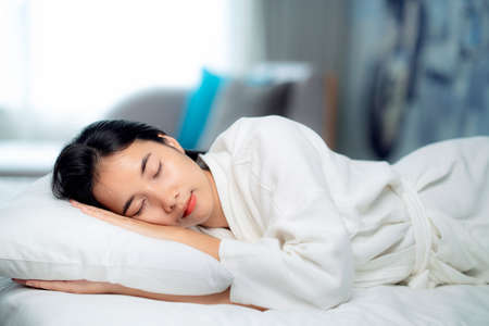 Asian traveller woman sleep and relax in hotel bed, this image can use for health, hotel, bed room and traavel concept