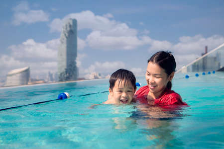 Asian Mother and baby swim in the roof top pool in they hotel in Bangkok city, Thailand