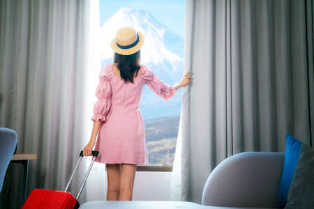Asian woman traveller arrive to room in hotel and open curtain for enjoy  view , this image can use for Travel, tour, hotel, japan, tokyo  concept
