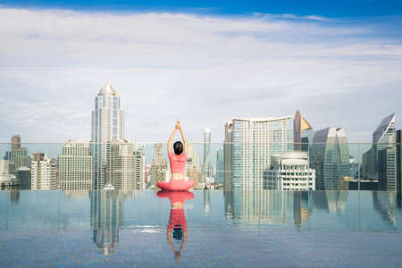Asian beautiful woman in pink sports uniform doing a yoga exercise on hotel rooftop with Bangkok city view and skyscraper background.