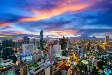 Bangkok city view from roof top of Hotel building with high building and sunset sky background. Imagens