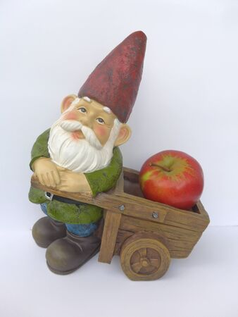 Garden dwarf with wheelbarrow and apple on isolated white background