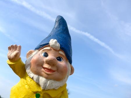 Garden dwarf with blue hat against blue sky