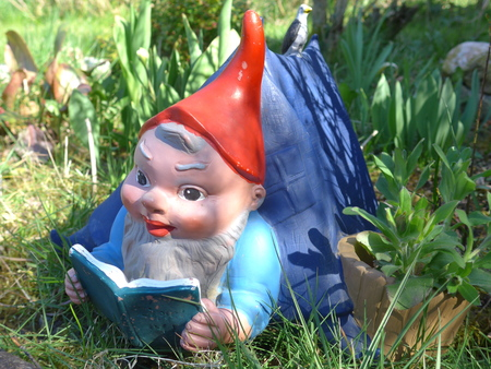 Garden dwarf lies in his tent on a green meadow and reads a book Stock fotó
