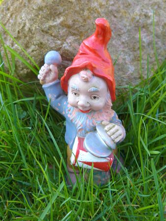 Garden dwarf with drum on a green meadow