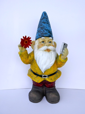 Garden dwarf with mobile phone and a red flower in his hand, isolated on a white background, makes a selfi