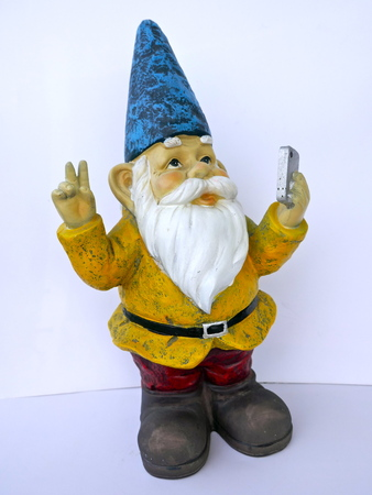 Garden dwarf with mobile phone, isolated on a white background, makes a selfi with peace sign