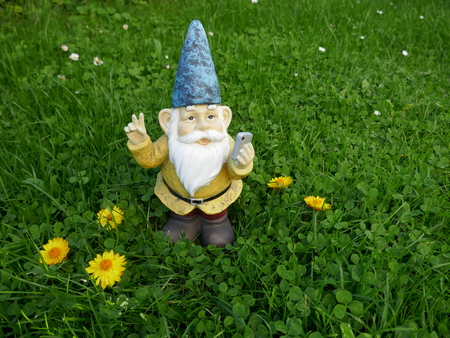 Garden dwarf with mobile phone on a green meadow makes peace sign