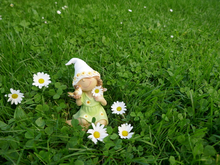 Little dwarf girl with a bird in her hands sits on a green meadow